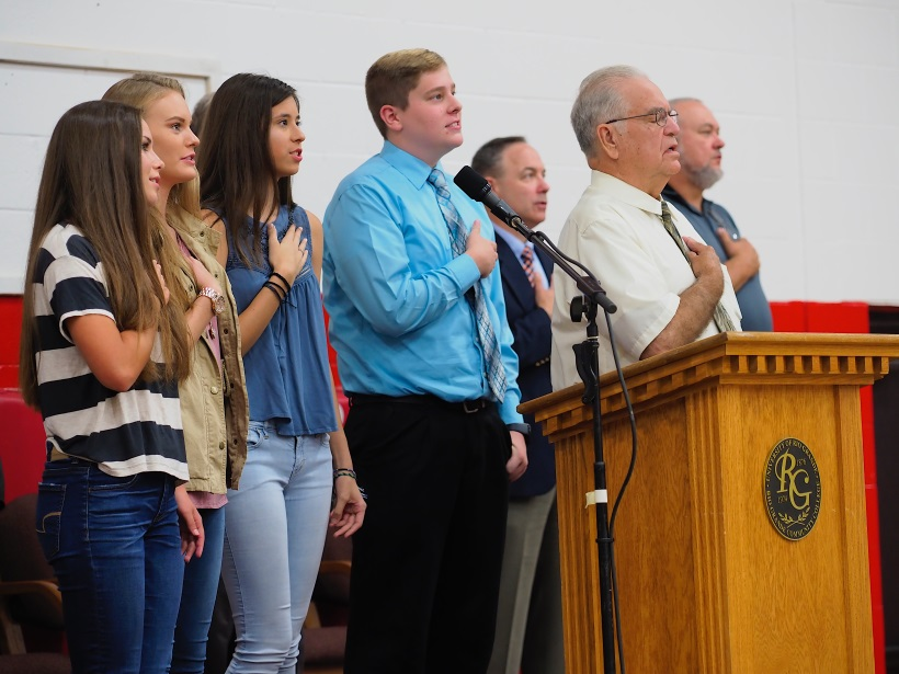 Students and Board Members saying Pledge of Allegiance.